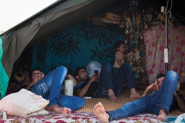 Syrian refugees on their cellphone in a camp, KRG.