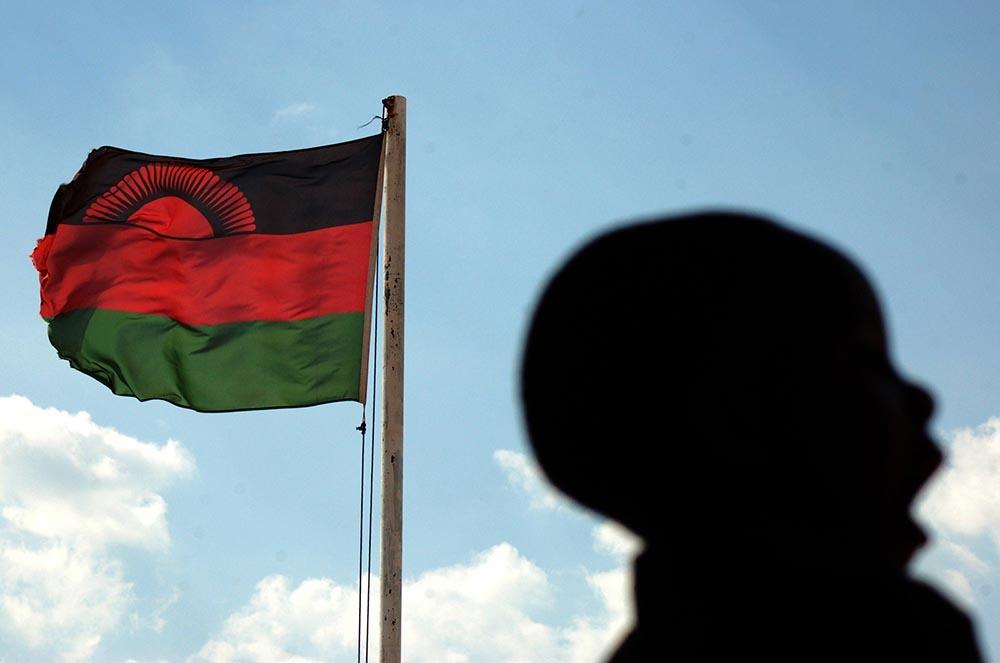 Malawian boy yawns in front of national flag