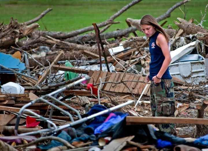 Girl looks through tornado debris