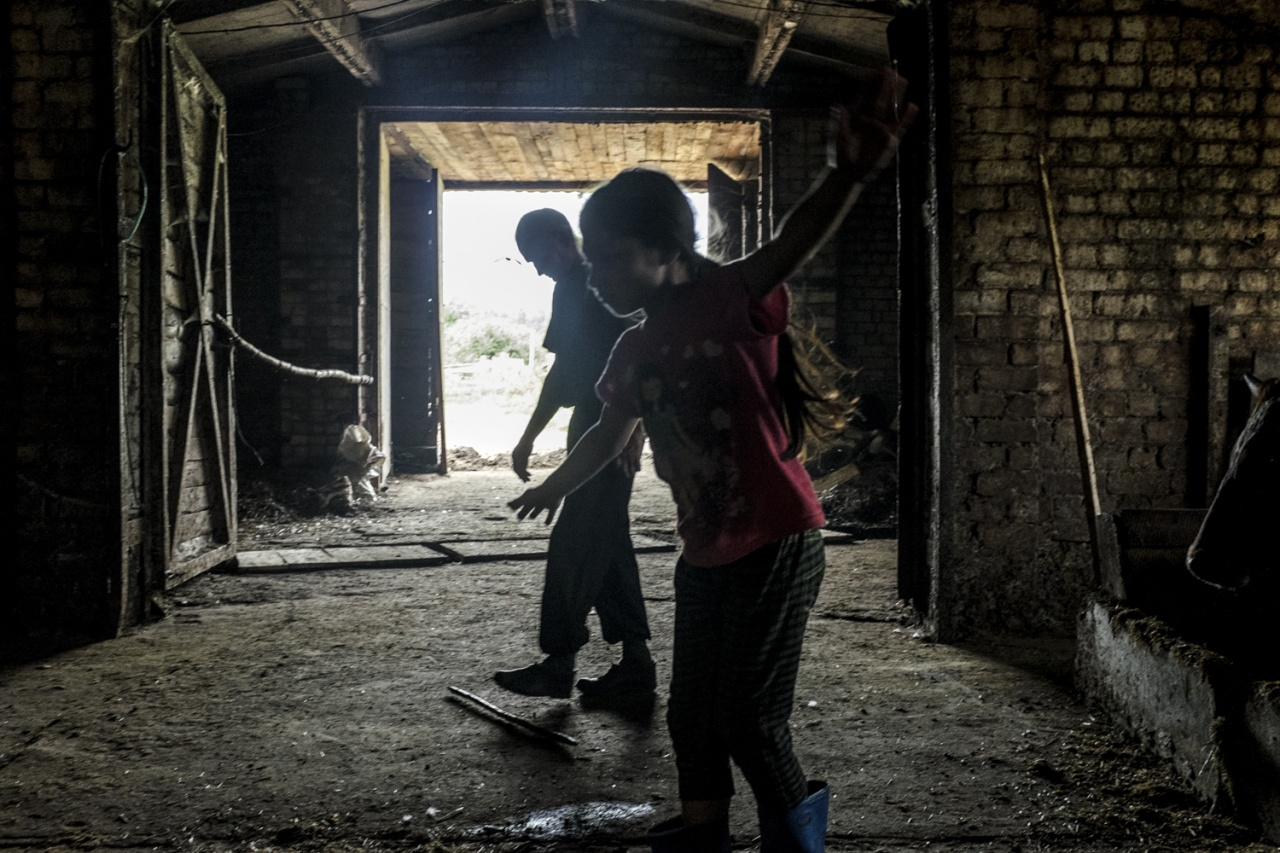 A girl is seen playing in a barn at a baptist farm