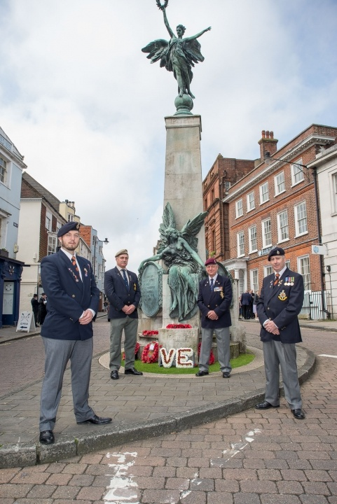 RBL members by war memorial during VE Day service.