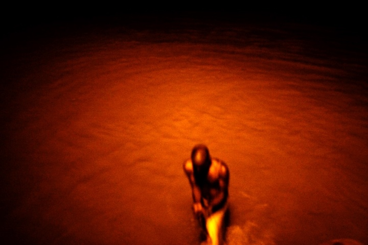 A man takes a dip after cremation in Ganges