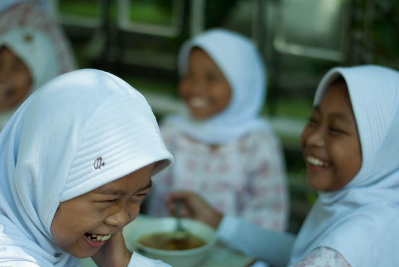 Indonesian school girls laughing at breakfast